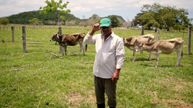 vídeos de stock e filmes b-roll de happy farmer smiling at camera man peasant in farm - américa do sul