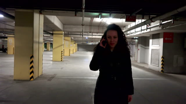 happy fashion girl walking and talking on phone in underground mall car parking lot. - basement stock videos & royalty-free footage