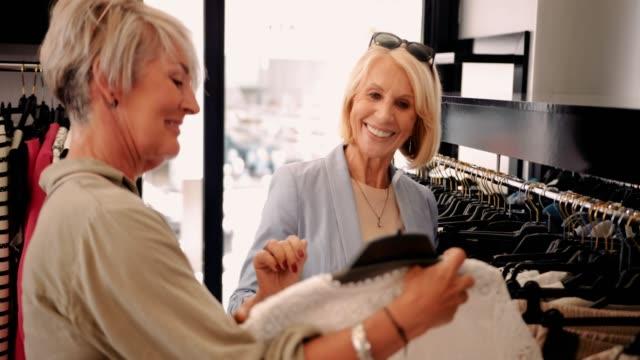 vídeos de stock, filmes e b-roll de felizes mulheres sênior na moda shopping para comprar roupas juntos - boutique