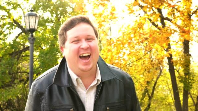Happy fat man laughs in the Park. Portrait video