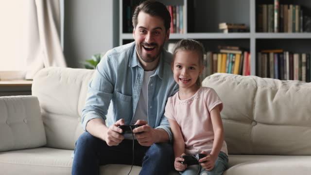 glad far och barndotter spelar tv-spel hemma - enbarnsfamilj bildbanksvideor och videomaterial från bakom kulisserna