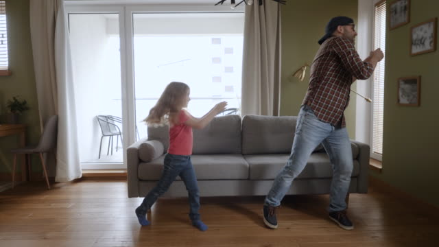 Happy Father and Daughter Dancing at Home Living Room, Fun Celebrating Funny Viral Dance Freedom Weekend. Family Enjoying Dance, Having Fun Party. Joyful Dad Daughter Dancing Cheerful In Living Room.