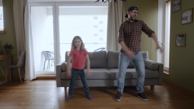 vídeos de stock, filmes e b-roll de pai e filha felizes dançando em casa sala de estar, diversão celebrando funny viral dance freedom weekend. família curtindo dança, se divertindo. filha de pai alegre dançando alegre na sala de estar. - pai e filha