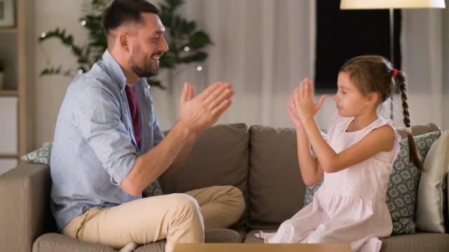 vídeos de stock, filmes e b-roll de pai feliz e filha jogando batendo palmas jogo em casa - fathers day
