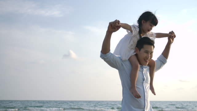 Video Happy father and daughter playing on the beach with blue sky background. Slow motion. Happy family concept.