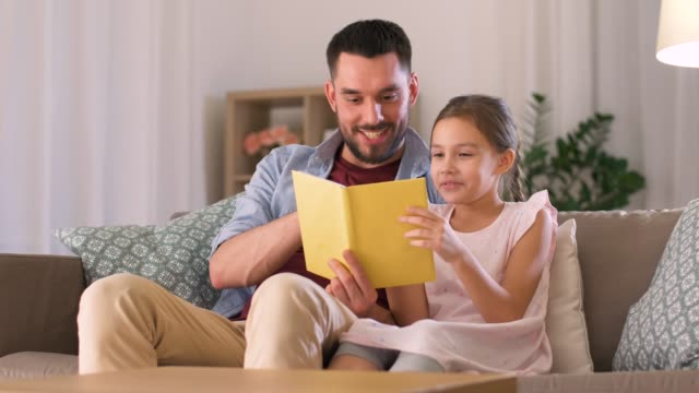 happy father and daughter reading book at home - spanish and portuguese ethnicity stock videos & royalty-free footage