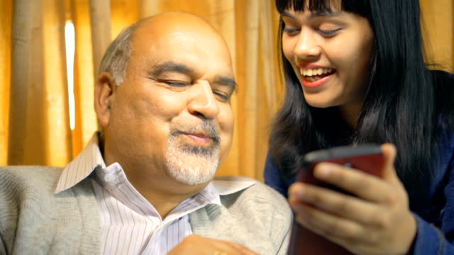 Happy father and daughter use and share a smartphone together. Indoor 4k video of happy father and daughter use and share a smartphone together at home in their leisure time. indian family stock videos & royalty-free footage