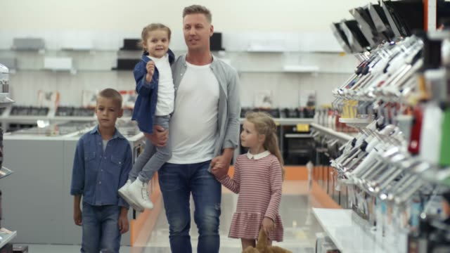 Happy Father and Little Kids Walking in Home Appliance Store