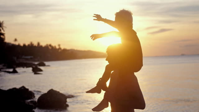 vídeos de stock e filmes b-roll de happy father and son in eyeglasses playing on tropical beach boy rising up hands imitating a flight at wonderful sunset in slow motion. 3840x2160 - bebé praia