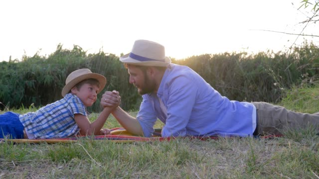 happy father and son kid play together in arm wrestling lying on plaid outdoors on background of sunset in rural video