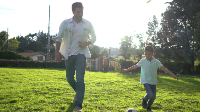happy father and son playing with a soccer ball at their backyard - баловство стоковые видео и кадры b-roll