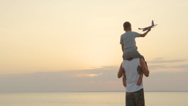 Gelukkige vader en zoon spelen met vliegtuig speelgoed samen bij zonsondergang gelukkig familie wandelen buitenshuis video