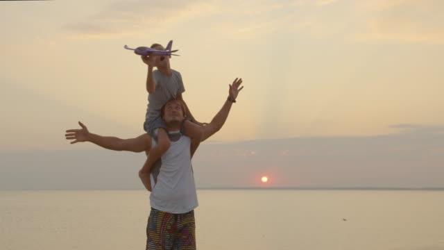 Glücklicher Vater und Sohn spielen mit Flugzeug Spielzeug zusammen bei Sonnenuntergang glückliche Familie zu Fuß im Freien – Video
