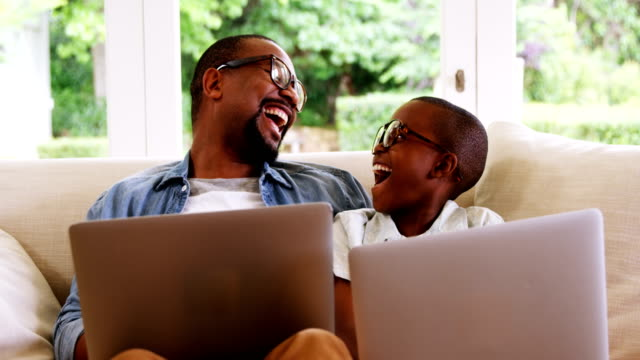 Happy father and son using laptop in living room
