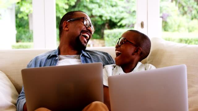 glücklicher vater und sohn mit laptop im wohnzimmer - brille stock-videos und b-roll-filmmaterial