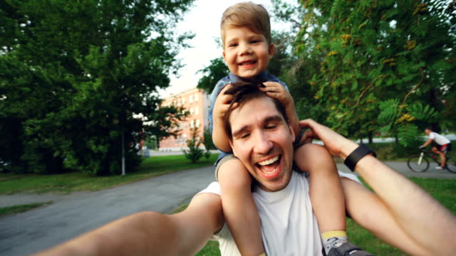 happy father carrying his smiling son on neck and making video selfie at smartphone camera during walk in park - selfie stock videos & royalty-free footage