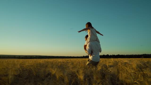 vídeos de stock, filmes e b-roll de pai feliz carregando a filhinha nos ombros no campo de trigo - dia dos pais
