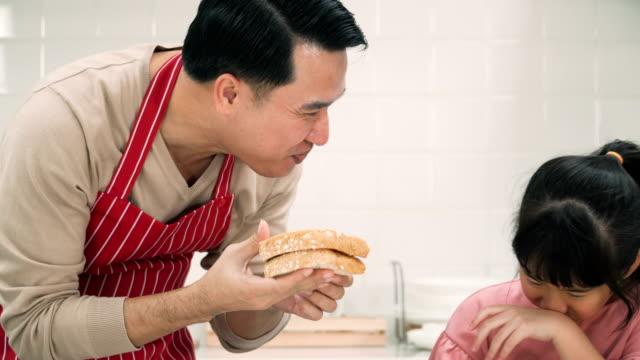 stockvideo's en b-roll-footage met gelukkig vader geven van dochter proberen te eten boterham met aardbei jam die dochter maken - geroosterd brood