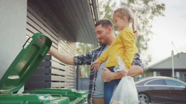 vídeos de stock e filmes b-roll de happy father holding a young girl and going to throw away an empty bottle and food waste into the trash. they use correct garbage bins because this family is sorting waste and helping the environment. - green city