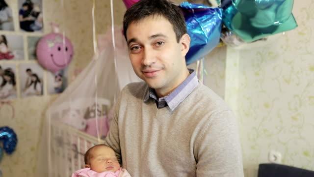 lycklig far innehav nyfödd baby i famnen. - enbarnsfamilj bildbanksvideor och videomaterial från bakom kulisserna