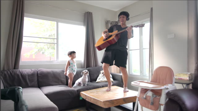 Happy father playing guitar with a son and two dogs in the living room at home.