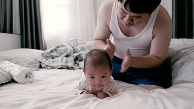 Père heureux jouant avec le fils de chéri sur le lit - Vidéo