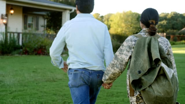 Happy female army soldier returns home Rear view of mid adult military soldier holds hands with her husband as they walk up to their home. The soldier has returned home from a military assignment. armed forces stock videos & royalty-free footage