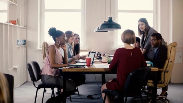 행복 한 여성 비즈니스 코치 직원 들에 게 가이드를 제공합니다. 사무실 보드 4 k 회의에서 테이블에 의해 다민족 팀워크 - 문화 스톡 비디오 및 b-롤 화면