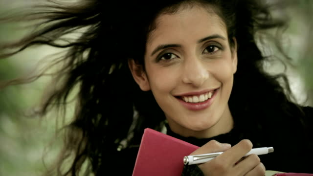 Happy female college student with book and pen. video