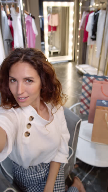 vídeos de stock e filmes b-roll de happy female customer making selfies in shop - vertical