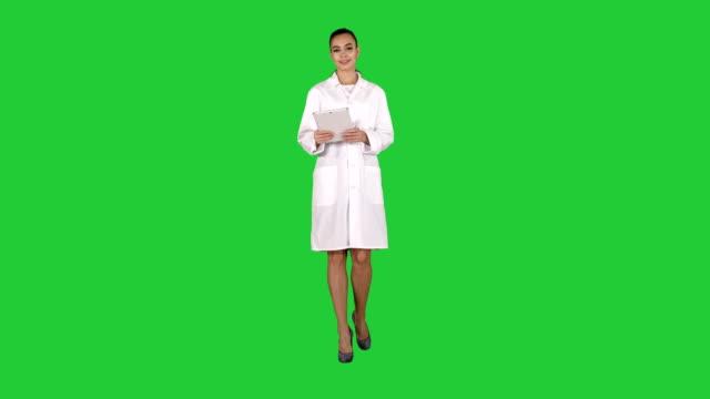 lycklig kvinnlig läkare som använder tablet pc vända sidor på den på en grön skärm, chroma key - aftonklänning bildbanksvideor och videomaterial från bakom kulisserna