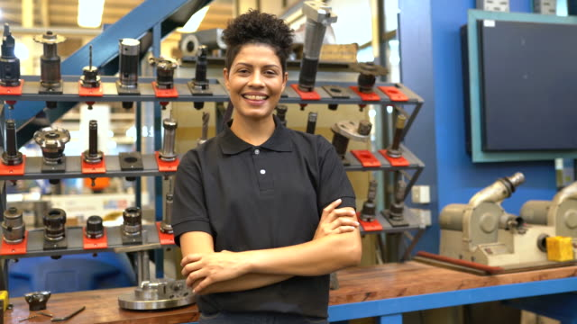 Happy female engineer standing in factory workshop Portrait of smiling woman employee standing with her arms crossed at factory shop floor. Happy female engineer standing by a rack of CNC tools in workshop. production line worker stock videos & royalty-free footage