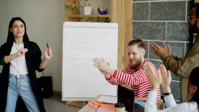 vídeos de stock, filmes e b-roll de empreendedor feminino feliz dançando e comemorando o sucesso do projeto de inicialização com multi étnica equipe no escritório moderno - festa da empresa