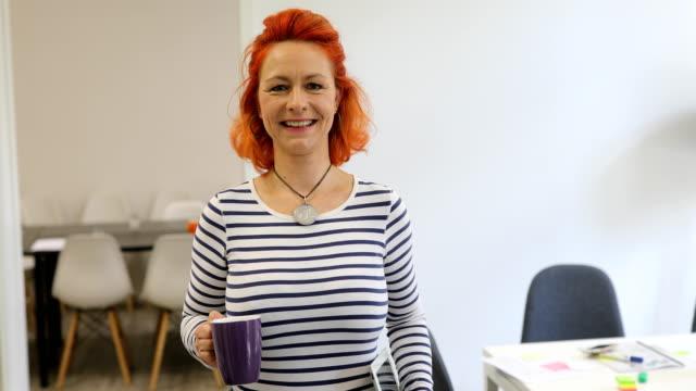 happy female executive with coffee mug and laptop - portret do pasa filmów i materiałów b-roll