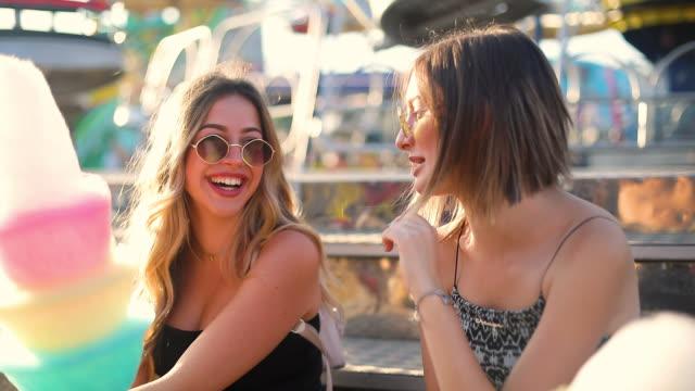 lyckliga kvinnliga vänner i nöjesparken äta sockervadd. två unga kvinnor som njuter av en dag på nöjesparken. - fritidsanläggning bildbanksvideor och videomaterial från bakom kulisserna