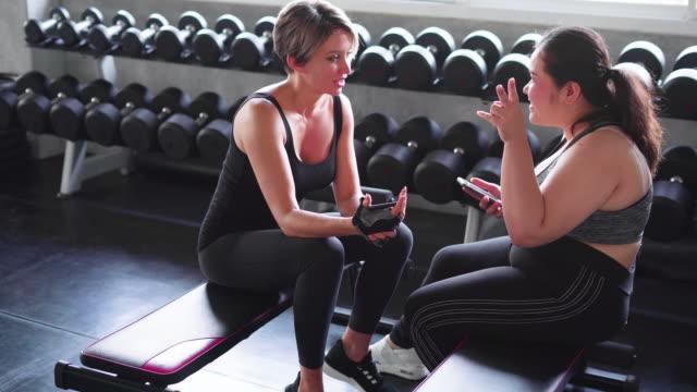 Happy female friends relaxing in gym