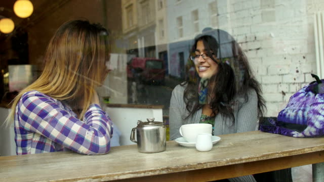happy female friends taking a coffee and talking sitting in a cafe video