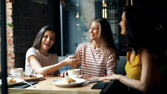 happy female friends talking then doing high-five and laughing in modern cafe - amicizia tra donne video stock e b–roll