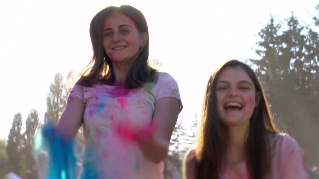 vídeos de stock e filmes b-roll de happy female friends throwing into air colorful powder, holi fest, slow-motion - holi