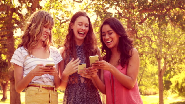 Happy female friends using their smartphones and laughing video