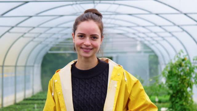happy female gardener in raincoat standing in greenhouse - gardening video stock e b–roll
