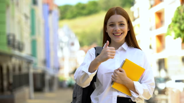 Happy female high-schooler with rucksack and books gesturing thumbs-up, student