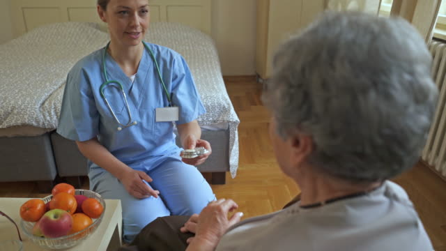 Happy female nurse giving prescription medicines to an old woman who is rejecting them and taking fruit instead. video