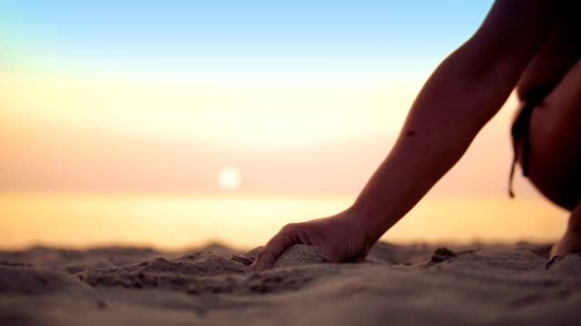 Happy female pours sand from the hand on sea beach sunset, concept of vacation, freedom, happiness, nature, travel, SLOW MOTION