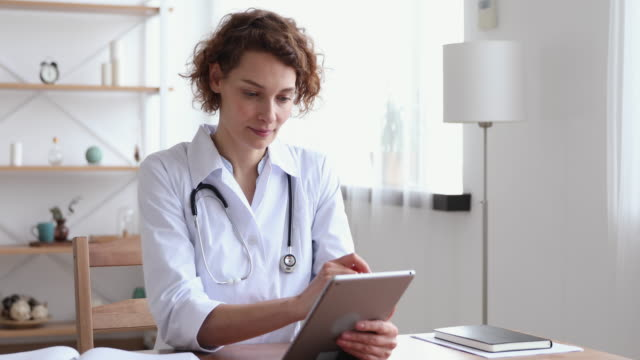 Happy female professional doctor using digital tablet at work Happy female professional doctor using digital tablet in hospital. Smiling young woman physician holding modern tech pad device working in medical office. Healthcare technology and medicine concept general view stock videos & royalty-free footage
