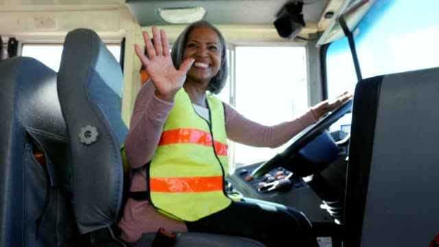 happy female school bus welcomes children onto school bus - bus driver stock videos and b-roll footage