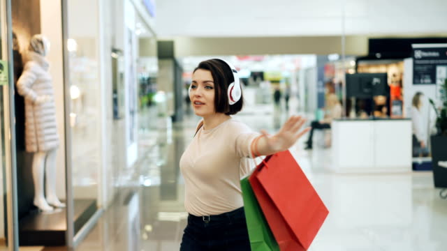 happy female shopaholic is having fun in shopping mall listening to music in headphones, dancing with bright bags and laughing pointing at goods in shop windows. - vendita al dettaglio video stock e b–roll