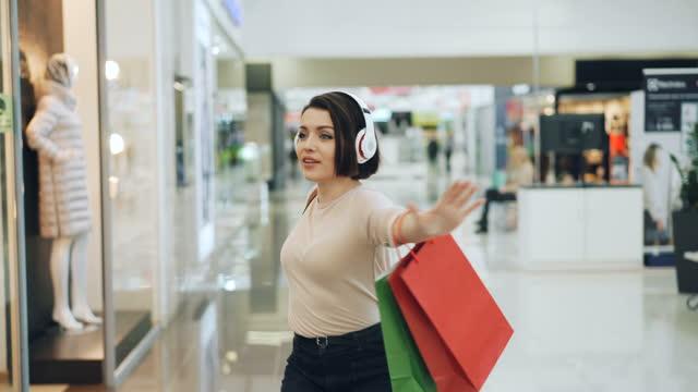 행복 한 여성 쇼핑 쇼핑몰 헤드폰에서 음악을 듣고, 밝은 가방 춤과 상점 창에 상품에서 가리키는 웃음에 재미를가지고 있다. - 쇼핑 스톡 비디오 및 b-롤 화면