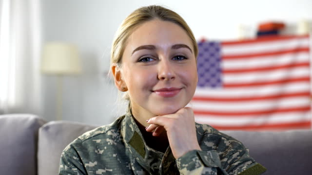 Happy female soldier in uniform smiling into camera, USA flag on background Happy female soldier in uniform smiling into camera, USA flag on background veteran stock videos & royalty-free footage