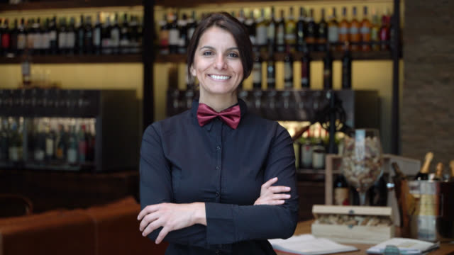 Happy female sommelier working at a wine bar looking at camera smiling